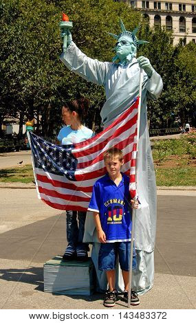 New York City - August 22 2004: Statue of Liberty Mime with American flag poses with tourists in Battery Park