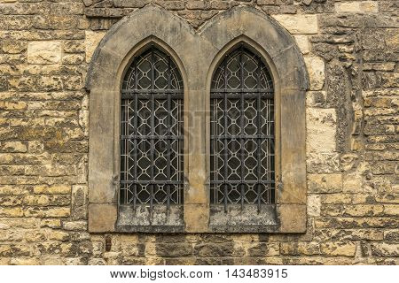 Church windows with bars - Architectural image with two windows from an old wall stoned church.