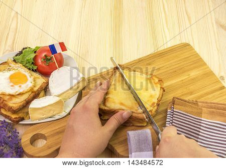 Woman's hand cutting french sandwich - Woman's hand cutting a croque monsieur a traditional french sandwich on a wooden table