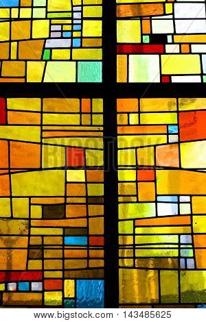 Image of a multicolored stained glass window with irregular block pattern in a hue of blue, square format