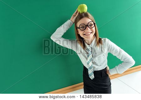 Amusing schoolgirl with an apple on her head. Photo teen girl near blackboard Education concept