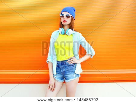 Fashion Pretty Woman With Headphones Over Colorful Orange Background