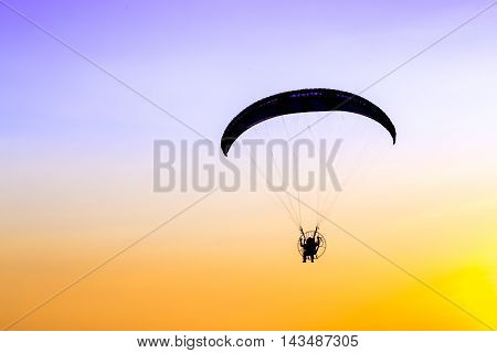 Glider Paramotor flying in the sky on twilight time