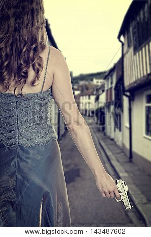 woman in gown with handgun on street