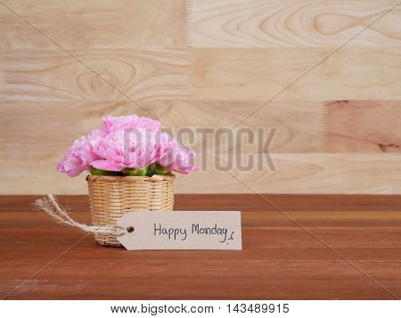 Pink Carnation flower in the basket and handwriting Happy Monday brown label with wood background