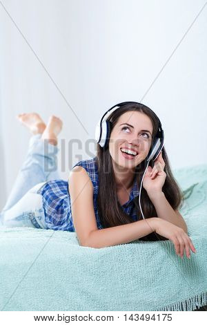 Happy girl listening music using headphones and singing on bed at home. People leisure and technology concept - happy woman or teenage girl in headphones listening to music. Beautiful girl in headphones