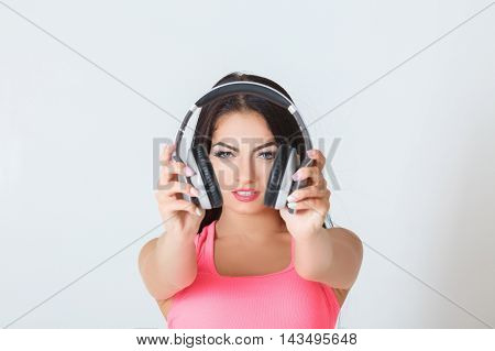 beautiful young woman holding headphones in his hand. focus on the girl's face