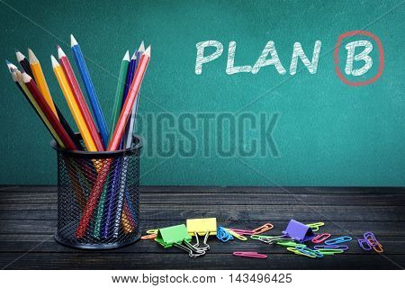 Plan B text on green board and group of pencils