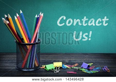 Contact us text on green board and group of pencils