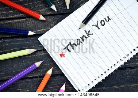 Thank you text on notepad and colorful pencils