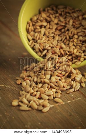 Fresh sunflower seeds spilling out of a yellow green bowl on a wooden table