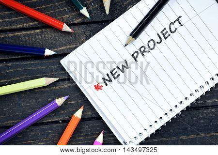 New Project text on notepad and colorful pencils