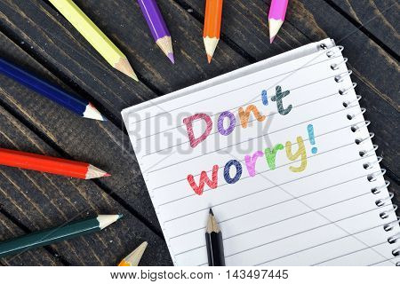 Don't Worry text on notepad and colorful pencils