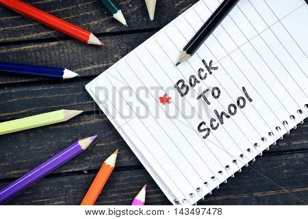 Back To School text on notepad and colorful pencils
