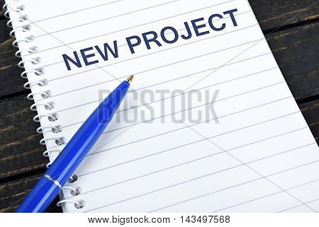 New Project text on notepad and blue pen