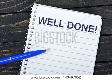 Well Done text on notepad and blue pen