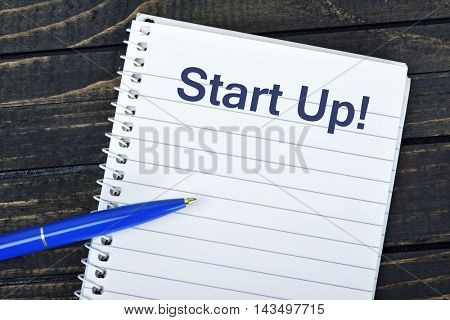 Start Up text on notepad and blue pen