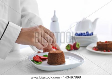 Chef decorating chocolate fondant with red currant, closeup