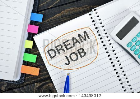 Dream Job text on notepad and hand calculator