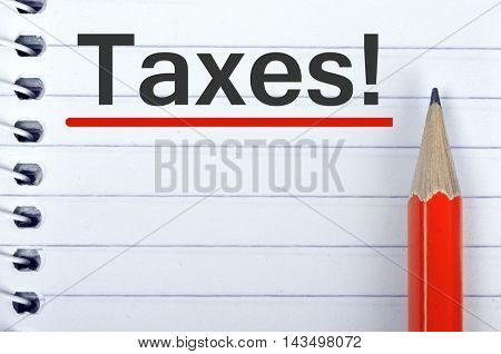 Taxes text on notepad and red pencil