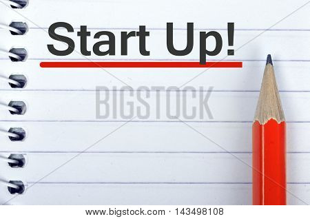 Start up text on notepad and red pencil