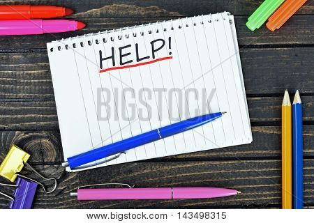 Help text on notepad and office tools on wooden table