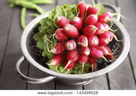 Heap of radishes in colander, closeup