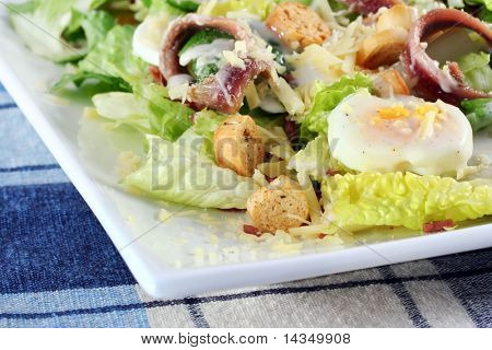 Fresh caesar salad on a white plate, with eggs, anchovies, croutons, bacon, and parmesan.