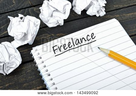 Freelance text on notepad and crippled paper