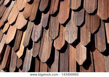 Protective wooden shingle on the roof. Roof made of wood. Close Up Wooden Tile Background