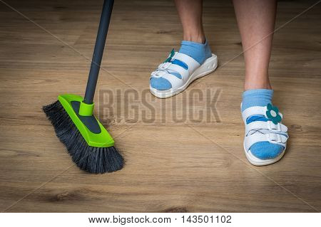 Woman With Broom Sweeping Wooden Laminate Floor