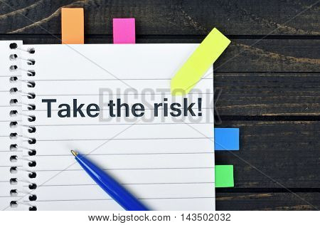 Take risk word on notepad and pen