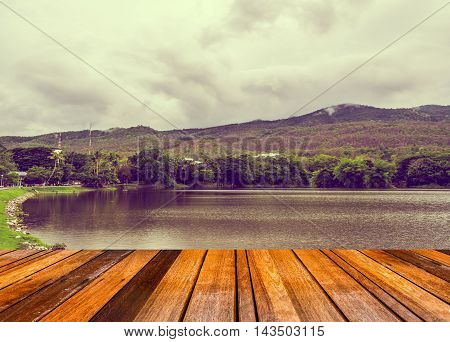 image of old wooden table with vintage tone image of lake with mountain and sky in background