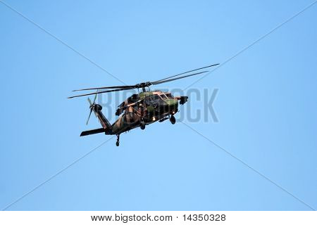 Blackhawk helicopter in flight against clear blue sky