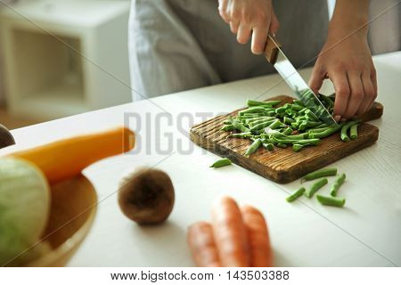 Woman cutting vegetables on kitchen
