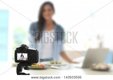Beautiful girl recording video on camera at kitchen. Food blogger concept