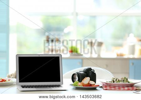 Laptop, tasty dish and camera on kitchen table. Food blogger concept