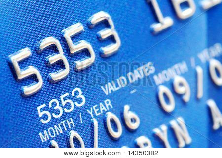 Macro of digits on a blue credit card.