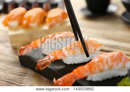 Tasty sushi with black chopsticks, closeup