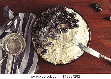 Appetizing cake decorated with blackberry on wooden table