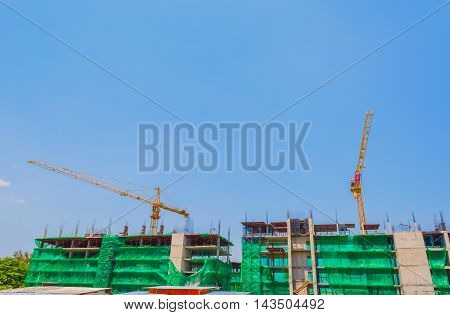 image of property construction site with cranes and clear blue sky for background usage.