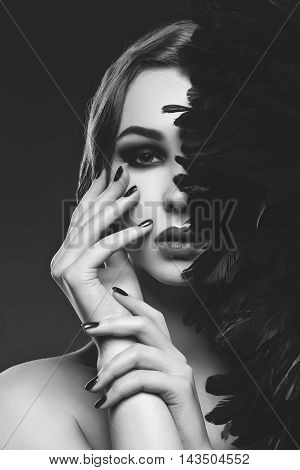 Beautiful young woman with smoky eyes and full red lips. Half of face covered with blue feathers. Studio closeup beauty shot. Copy space. Monochrome.