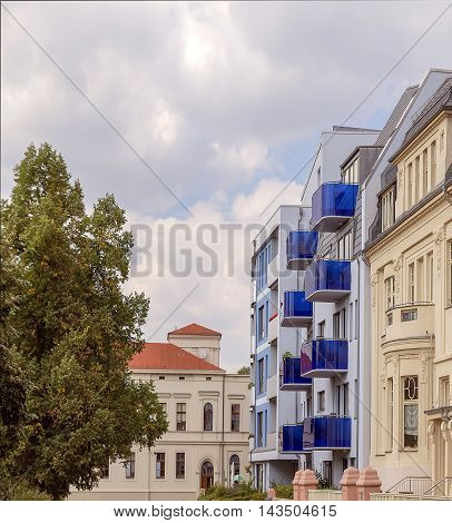 The contrast of a new building with blue balconies, the building of the old architecture