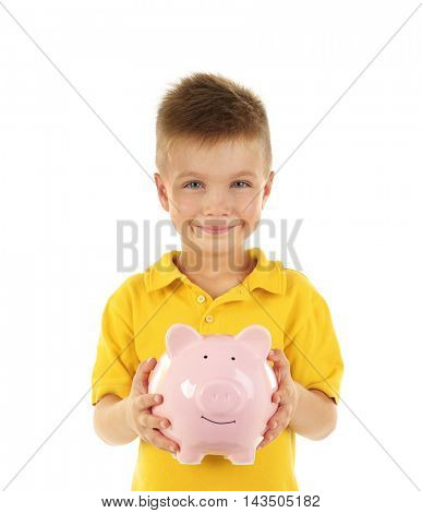 Savings concept. Cute boy in yellow T-shirt holding piggy bank isolated on white