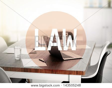 Law concept. Workplace with laptop and text design. Word law on conference office background.