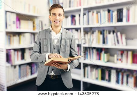 Young man with book on blurred book shelves background.