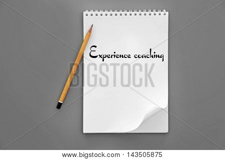 Notebook and pencil on grey background. Experience coaching concept