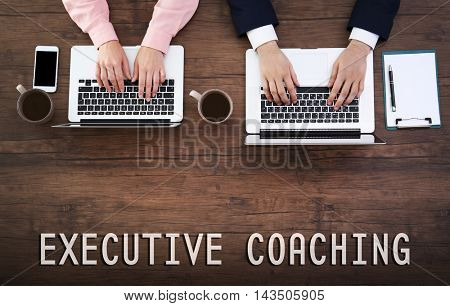 Man and woman working on laptops. Executive coaching concept
