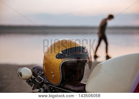 Close up of motorcycle with american flag and golden helmet with a man on the backgroud walking