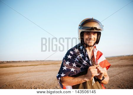Young smiling brutal man wearing american flag cape and golden looking at camera
